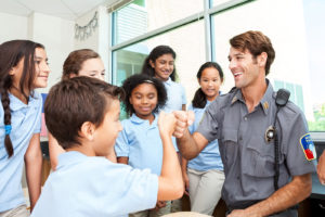Friendly police officer gives fist bump to student